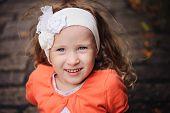 pic of headband  - beautiful smiling child girl portrait in white headband and orange cardigan with stone road on background - JPG