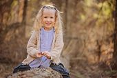 foto of early spring  - horizontal portrait of adorable smiling blonde child girl in blue shirt on the walk in early spring forest - JPG