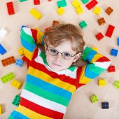 stock photo of indoor games  - Little blond kid boy playing with lots of colorful plastic blocks indoor - JPG