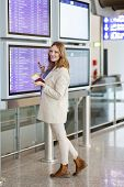 picture of terminator  - Young woman at international airport checking electronic board and waiting for her flight - JPG