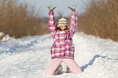 foto of knee-cap  - Happy young girl standing on knees and with hands up on snow - JPG