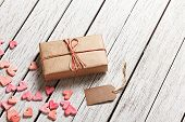foto of wood craft  - Vintage gift box with blank gift tag and heap of small hearts on white wooden background - JPG