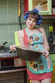 stock photo of nuke  - The young housewife on kitchen cooks food near to an electric stove - JPG