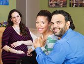 foto of hispanic  - Smiling Hispanic couple sitting with beautiful surrogate mother - JPG