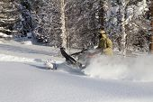 foto of ural mountains  - Athlete on a snowmobile moving in the winter forest in the mountains of the Southern Urals - JPG