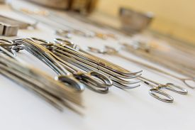 pic of scalpel  - surgical instruments and tools including scalpels forceps and tweezers arranged on a table for a surgery