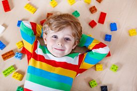 picture of daycare  - Little blond child playing with lots of colorful plastic blocks indoor - JPG