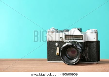 Retro camera on table on green background