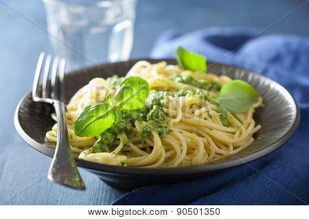 spaghetti pasta with pesto sauce over blue