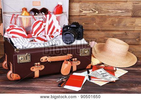 Packed suitcase of vacation items on wooden background