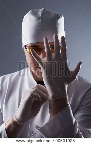 Male Doctor In Cap And Glasses Wear Rubber Medical Gloves In Contrasting Light