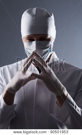Male Doctor In Cap And Mask Wear Rubber Medical Gloves In Contrasting Light