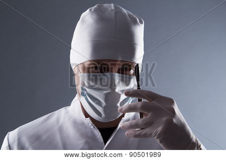 Male Doctor In Cap, Mask And Rubber Medical Gloves Holding Scalpel