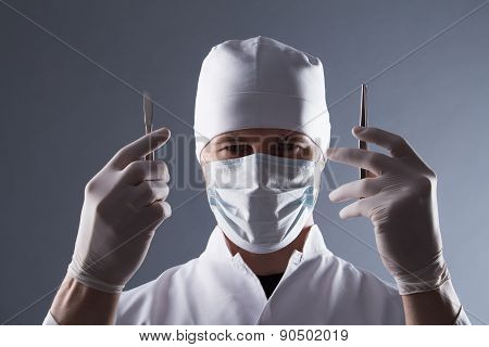 Male Doctor In Cap, Mask And Rubber Medical Gloves Holding Scalpel And Pincers
