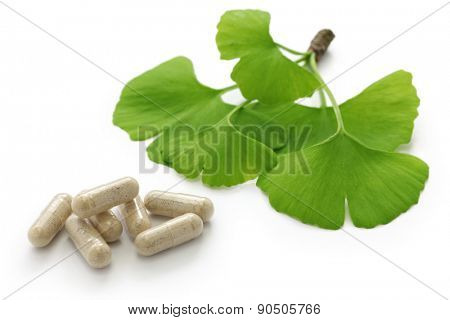 ginkgo biloba leaves and medicine capsule pills on white background