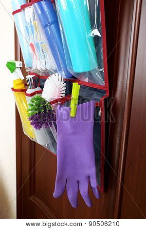 Household chemicals in holder hanging on wooden door background