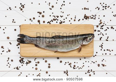 Trout fish on cutting wooden board with peppercorns