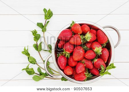 Mint and strawberries in rustic colander on white wooden table