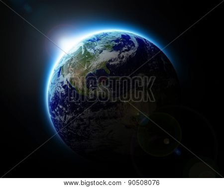 Sun rising over blue planet Earth as seen from space