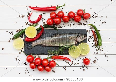 Trout Fish On Cutting Board With Cherry Tomatoes And Lemon
