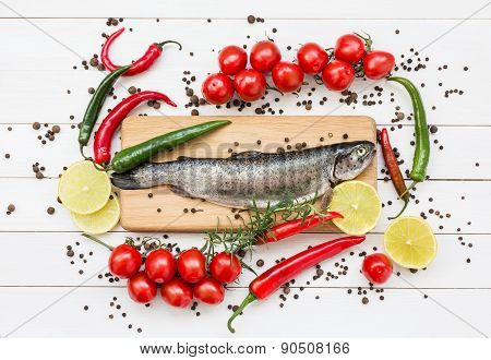 Trout Fish On Wooden Cutting Board With Cherry Tomatoes