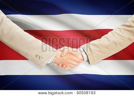 Businessmen Handshake With Flag On Background - Costa Rica