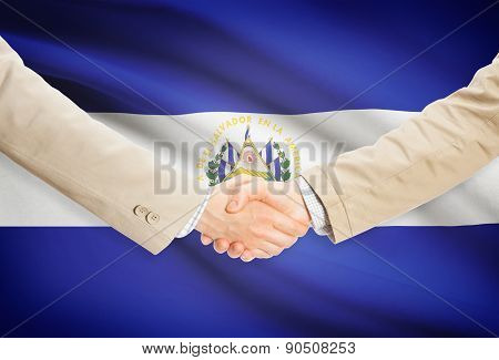 Businessmen Handshake With Flag On Background - El Salvador
