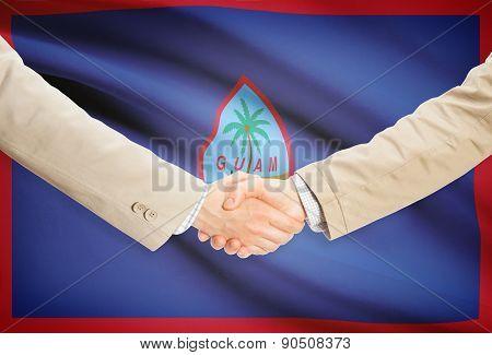 Businessmen Handshake With Flag On Background - Guam