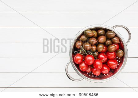 Cherry Tomatoes In Rustic Colander On White Wooden Table