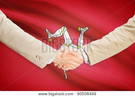 Businessmen Handshake With Flag On Background - Isle Of Man