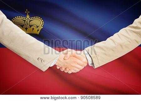 Businessmen Handshake With Flag On Background - Liechtenstein