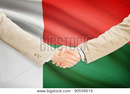 Businessmen Handshake With Flag On Background - Madagascar