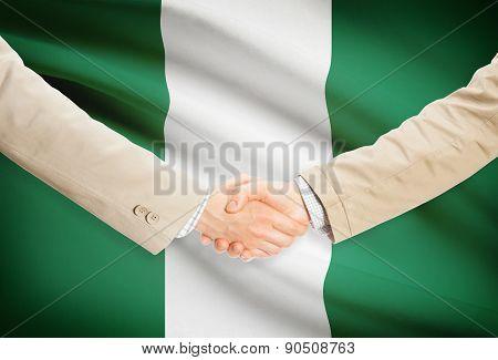 Businessmen Handshake With Flag On Background - Nigeria
