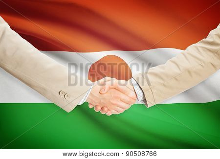Businessmen Handshake With Flag On Background - Niger