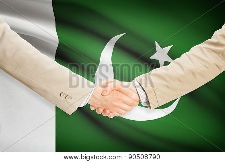 Businessmen Handshake With Flag On Background - Pakistan