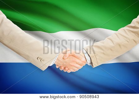 Businessmen Handshake With Flag On Background - Sierra Leone