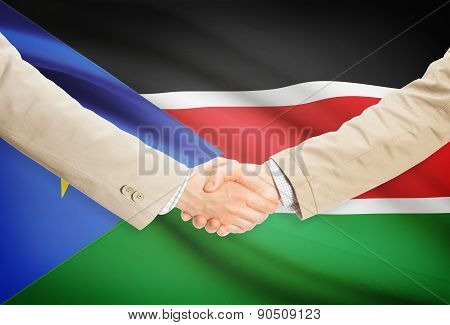 Businessmen Handshake With Flag On Background - South Sudan