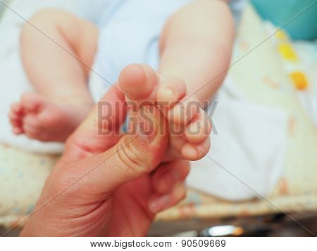 Baby Receiving Foot Massage After Diaper Change With A Thumb