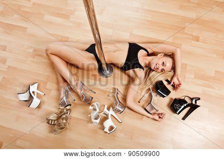 Young Slim Pole Dance Blond Woman Lies On Floor Near Pool