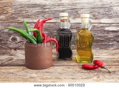 Olive Oil And Vinegar In Glass Bottles, Chilly Pepper  On Wooden Background. Toned