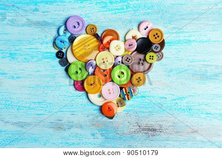 Sewing buttons heart on wooden background