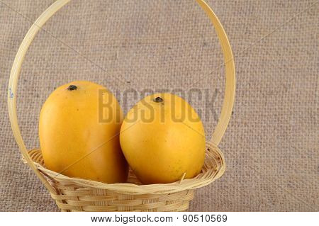 Mango fruit in basket on sack cloth