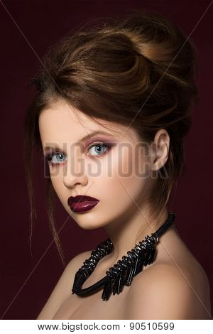Young pretty girl with vinous lipstick posing at dark red background