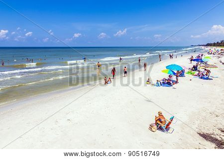 People Enjoy The Beautiful White Beach At Naples Pier