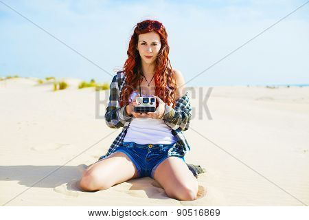 Beautiful Young Woman With Instant Camera In The Beach