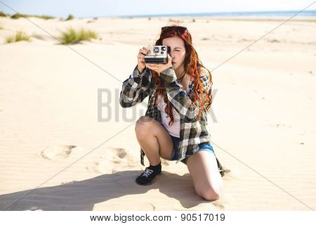 Young Woman On The Beach With Instant Photo Camera