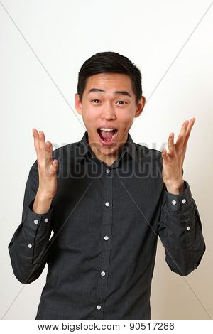 Laughing young Asian man gesturing with hands and looking at camera.
