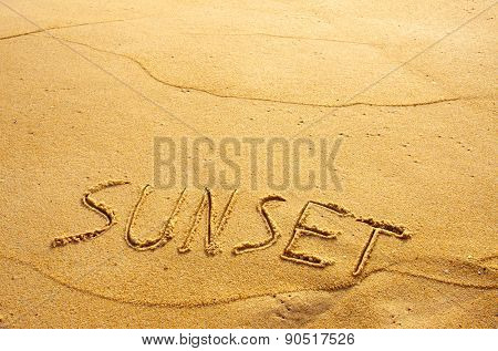 Summer concept of beach with word sunset written on the sand