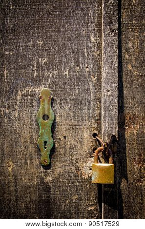 Detail of a old scratched wooden door with rusty padlock