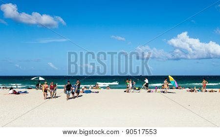 Tourists On Beach Enjoying Sun In South Beach